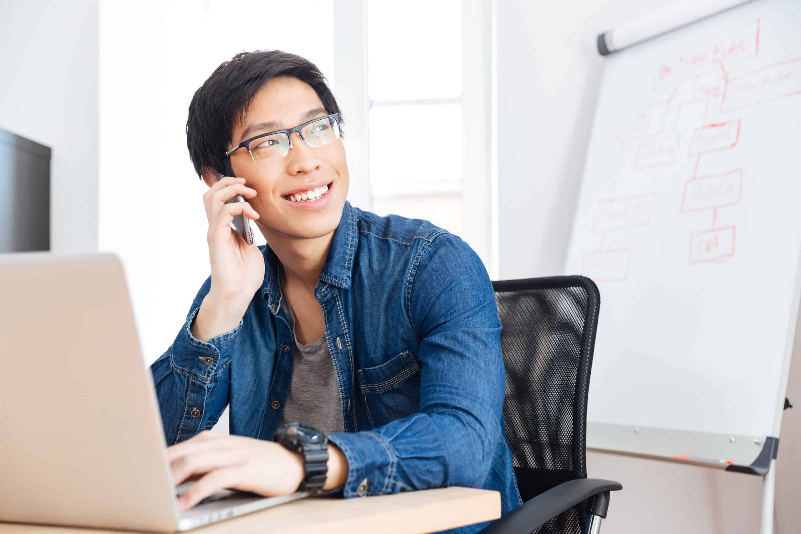 Smiling young businessman with laptop talking on mobile phone